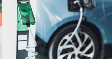 Blaues Elektrofahrzeug an einer Aufladestation - Steuern sparen mit einem Elektroauto