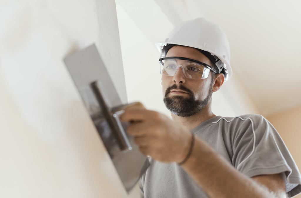 Professioneller Handwerker spachtelt die Wohnzimmerwand