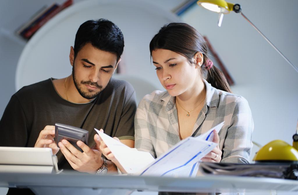 Junges Paar in der Erstausbildung sitzt zusammen und machen die Steuererklärung