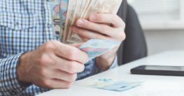 Mann zählt Geld im Büro zu Coronazeiten - Kurzarbeitergeld